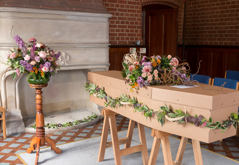 Coffin with garland, bouquet and Vase